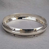 Half-inch wide sterling silver bangle with hand stamped Feather design.  Native American made.