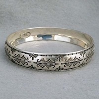 Half-inch wide sterling silver bangle with hand stamped Butterfly design.  Native American made.