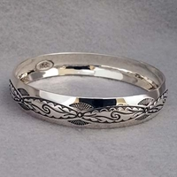 Half-inch wide sterling silver bangle with hand stamped Pueblo Scroll design.  Native American made.