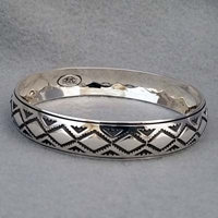 Half-inch wide sterling silver bangle with hand stamped Diamond Back design.  Native American made.